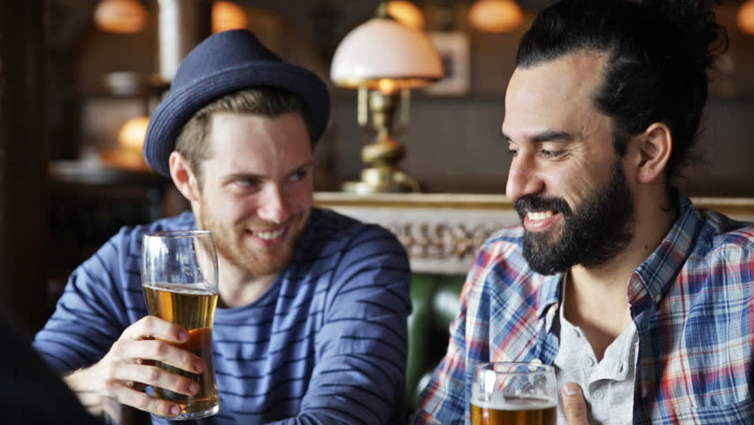 people, toast, leisure, friendship and celebration concept - happy male friends drinking beer and clinking glasses at bar or pub