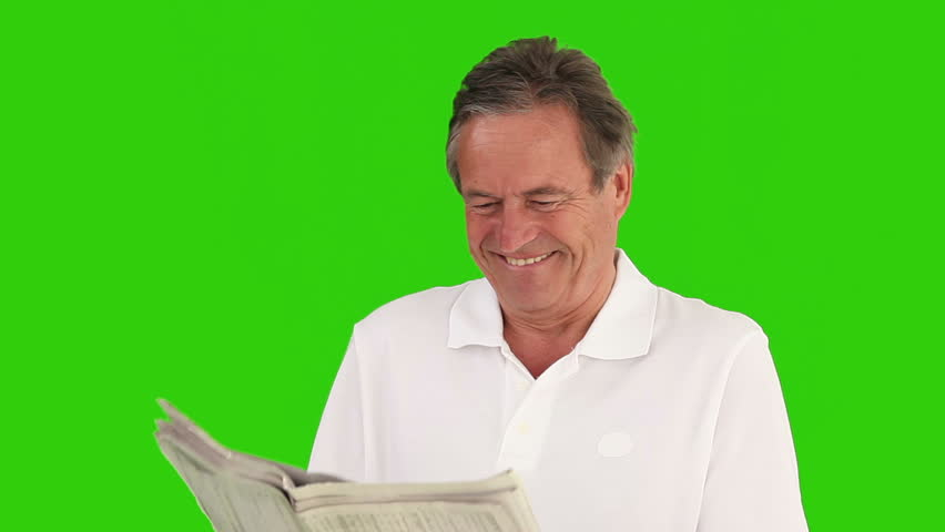 Retired man reading a pleasant article in the newspaper against a green screen