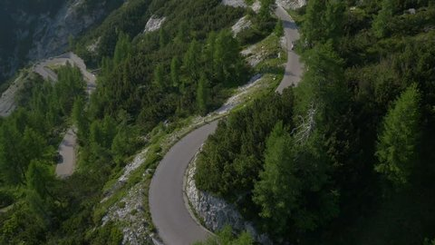 Aerial - Car driving over hairpin turns on mountain road