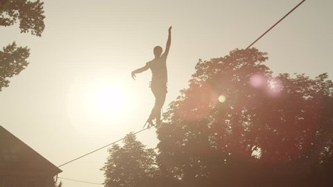 SLOW MOTION: Young man balacing on slackline between the houses in big city at beautiful sunset