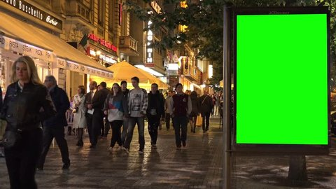 PRAGUE, CZECH REPUBLIC - MAY 30, 2015: billboard in the city - urban street with buildings - green screen - people