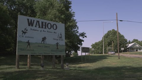 Static shot of the WAHOO, Nebraska sign as a car drives by in the background.