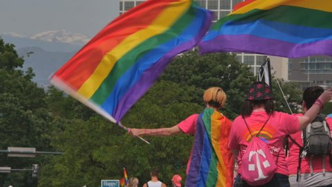 DENVER, COLORADO - CIRCA JUNE 2015. Gay Pride Parade supporters wave rainbow flags with the Rocky Mountains in the background. Slow motion. Symbol of LGBT GLBT transgender rights love equality
