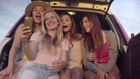 Group Of Wild And Fun Teens Hang Out In Back Of SUV, Girl Grabs Friend's Phone To Take Selfies (4K)