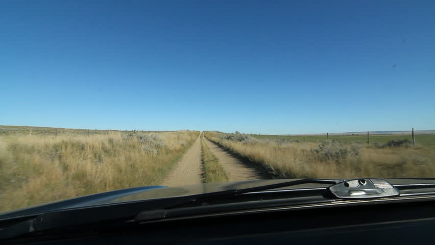 Driving on rough road between two fields. Saskatchewan, Canada. Note: some smudges on windshield.