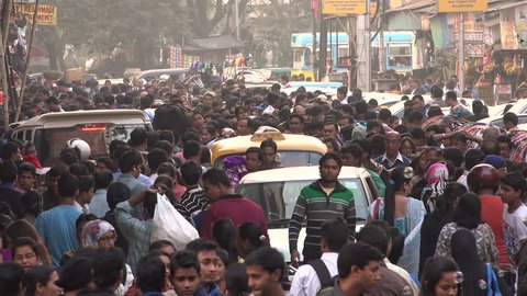 KOLKATA, INDIA - 13 DECEMBER 2014: Large numbers of people walk through a busy shopping street and popular market in central Kolkata, one of India's largest cities.