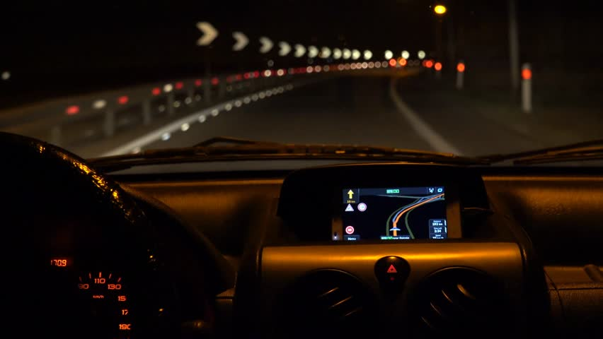 Car driving at night with illuminated dashboard and navigation, POV UHD 4K stock footage