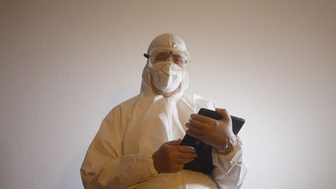 BIOHAZARD LAB TECHNICIAN with tablet computer looking at camera.
