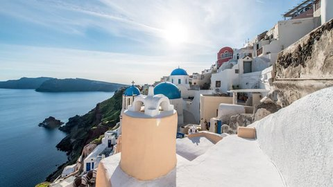 Blue domed churches and white-washed houses in the village of Oia on the edge of the volcanic caldera on the island of Santorini in Greece.