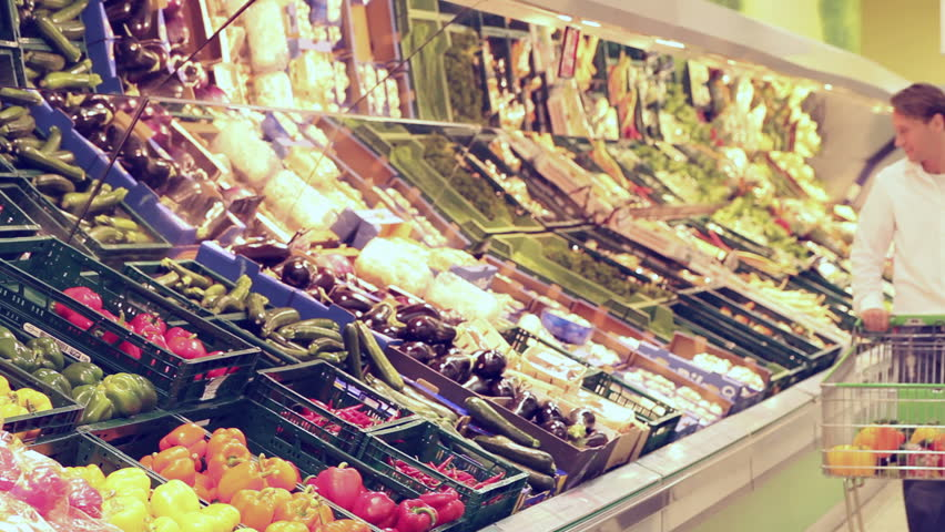Man shopping vegetables in a supermarket, he is walking from outside the focus to the inside | Shutterstock HD Video #1092778