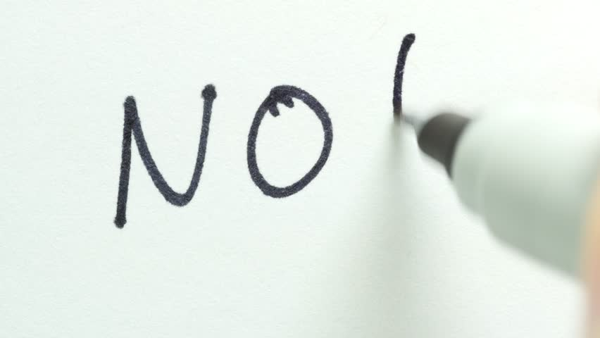 Writing NO on a sheet of paper.