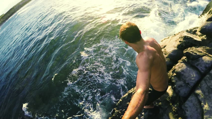 Athletic Young Man Jumping from Sea Cliffs into the Blue Ocean in Hawaii at Sunset.