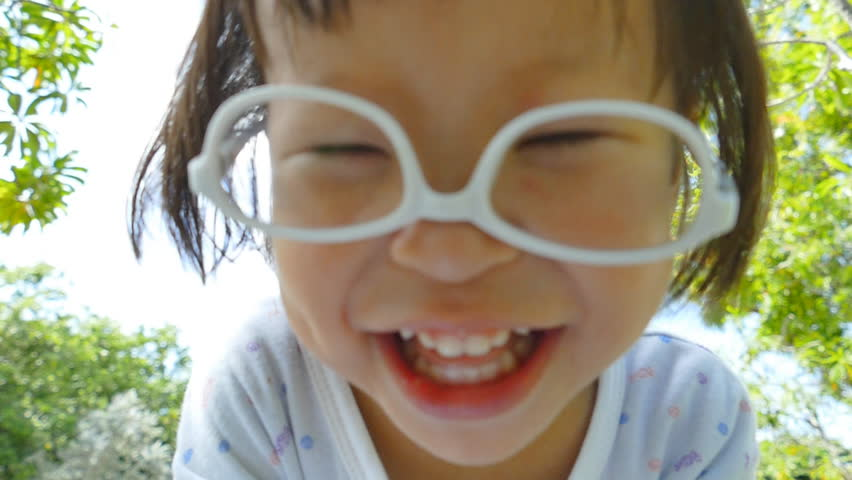 Little Girl wearing glasses and laughing at camera , slow motion    Shutterstock HD Video #10999118