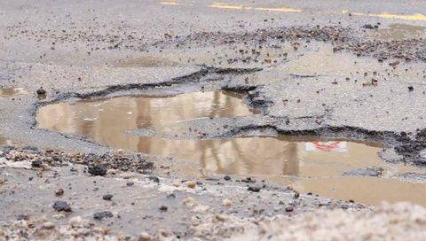 Car driving over a pothole