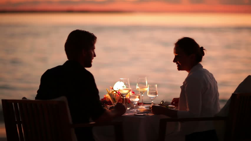 young couple dining and feeding each other on a tropical beach at sunset with audio