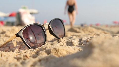 Points lying on the sand. In the sunglasses reflected the sun, sky and the human walking on the beach