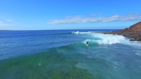 AERIAL: Flying in front of young surfer surfing on big wave on a beautiful sunny day in Canary Islands