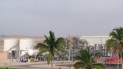 A pan of industrial buildings in an industrial area in Salalah in Oman, showing date trees and the desert background.