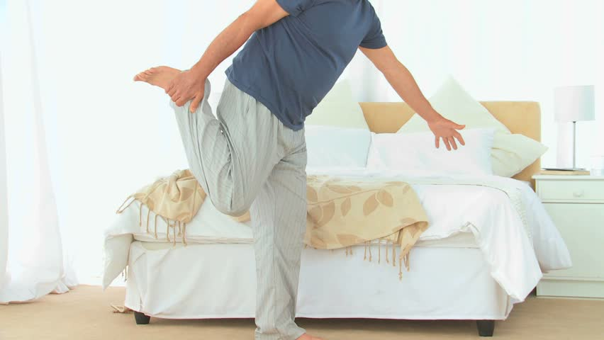 Senior man stretching himself in his bedroom