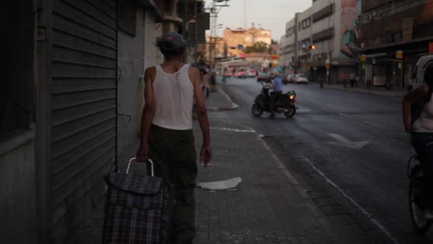 TEL AVIV, ISRAEL - CIRCA SEPTEMBER 2012 - Poor man walks on sidewalk in Tel-Aviv