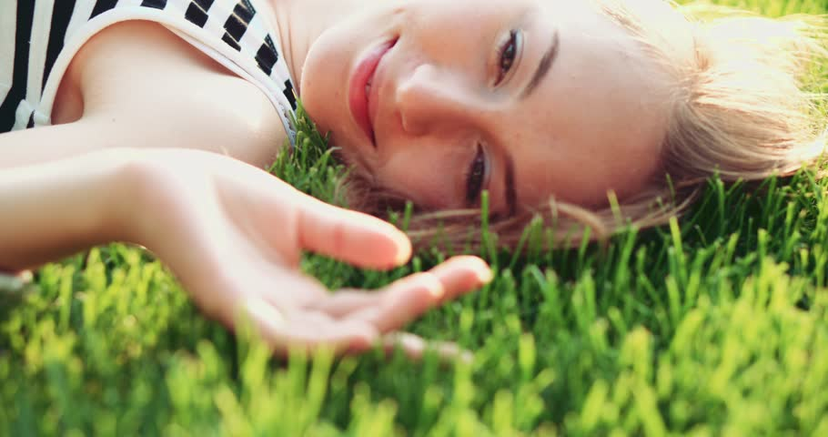 Beautiful young woman lying on the meadow smiling and dreaming. Slow Motion, 4K. Enjoy nature. Beauty girl on the green grass outdoors turning to the camera, close up. Spring or summer lawn.  #11142368