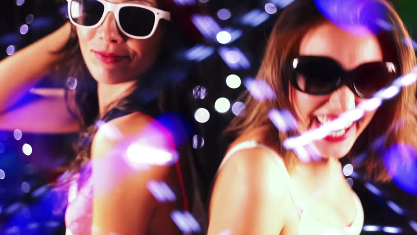 two sexy woman dancing together in front of disco style lights