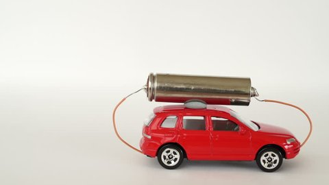 Electric car, toy car with a battery on the roof. A small toy car with a AA battery on the roof rolls into the frame.