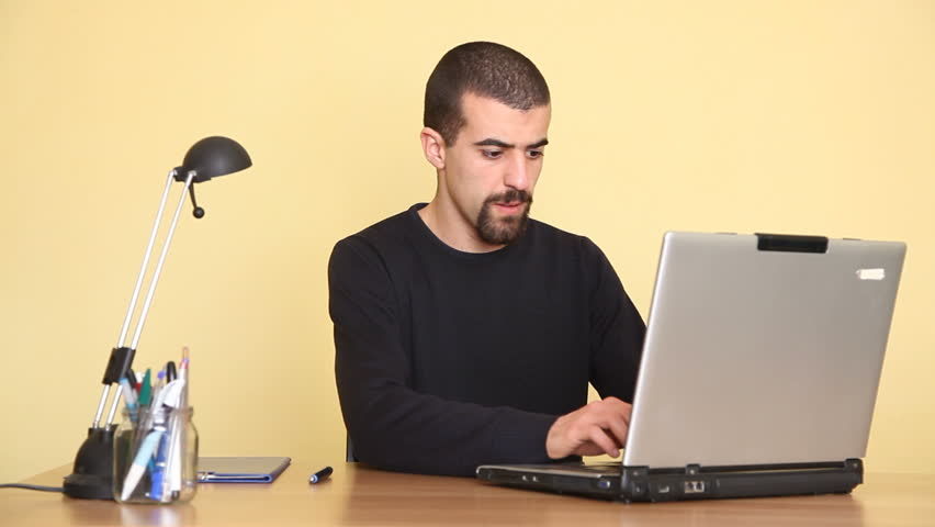 Man Typing on computer and writing, thumb up