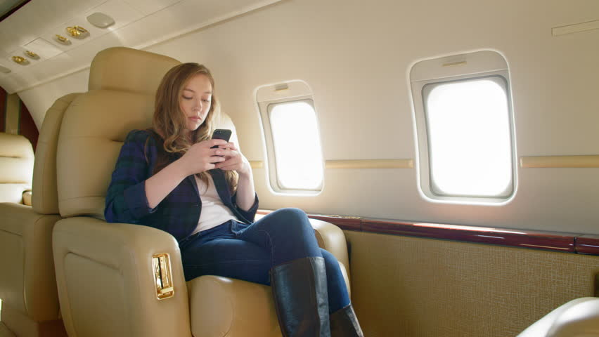 Attractive brunette wearing smart jacket uses phone to text, make notes or play games while sitting on an executive jet.  Wide view, slow motion, originally recorded in 4K at 60fps.