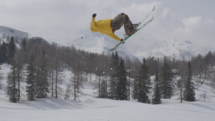 AERIAL SLOW MOTION: Freestyle skier jumping over big air kicker in sunny winter in ski resort
