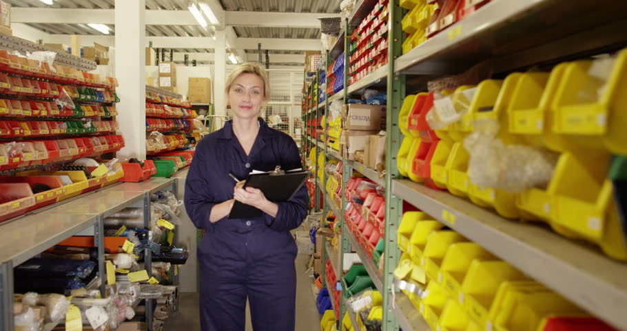 Portrait of an attractive female worker with a clipboard standing in a distribution warehouse | Shutterstock HD Video #11266418