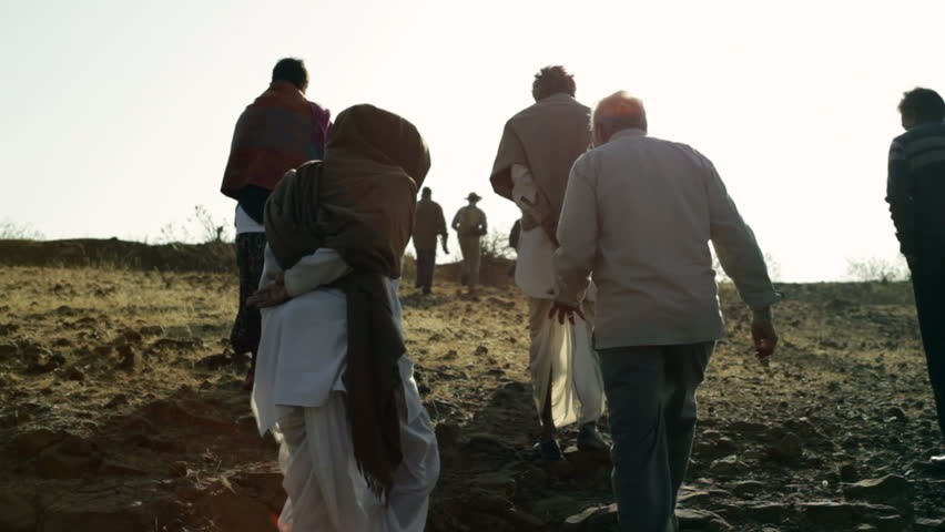 ANDHRA PRADESH, INDIA - CIRCA MAY 2013 - Traditional village elders walk up dry desert land, long shot, lens flare
