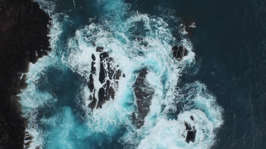Aerial of the ocean waves washing up on a black basalt rock in Hawaii. | Shutterstock HD Video #11290640