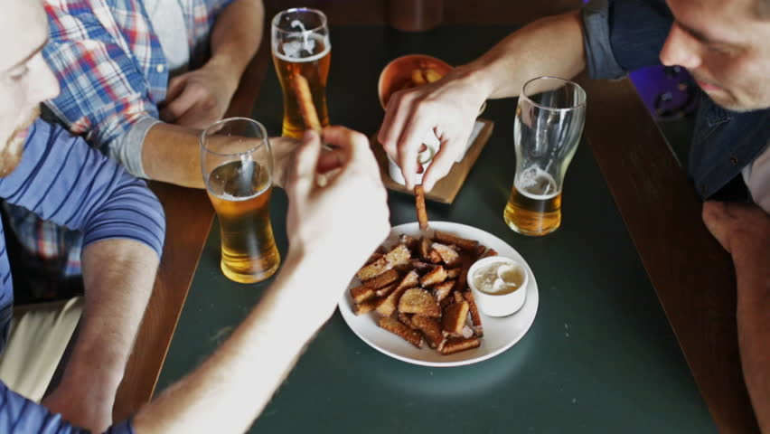 people, men, leisure, friendship and communication concept - happy male friends drinking beer and eating snacks a at bar or pub