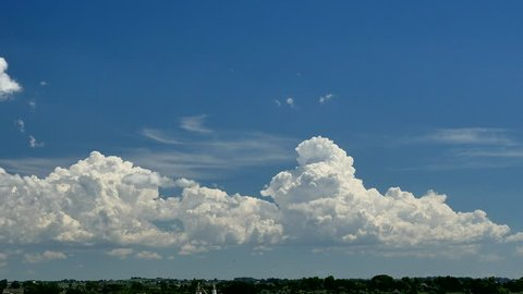 Developing Thunderstorms. Cumulus clouds build into congestus and then small cumulonimbus with anvils on a hot summer day.