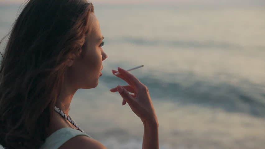 Girl smoking cigarette at sunset near the sea