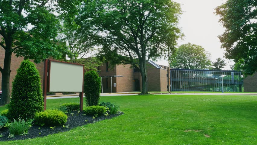 A daytime establishing shot of a generic high school with a blank sign for customization.
