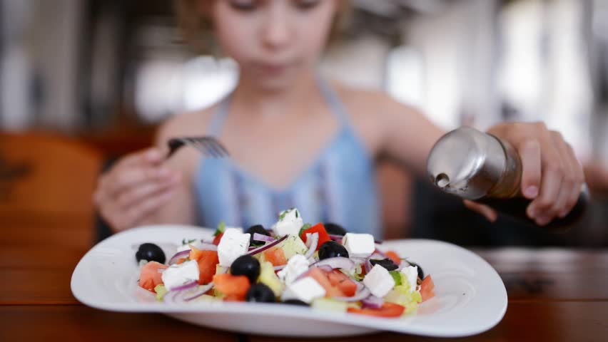 Girl pouring balsamic sauce Greek salad in a restaurant.
