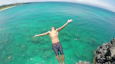 Young Man Back Flips off Cliff Into Water. Summer Extreme Sports Fun Lifestyle. (Slow Motion)