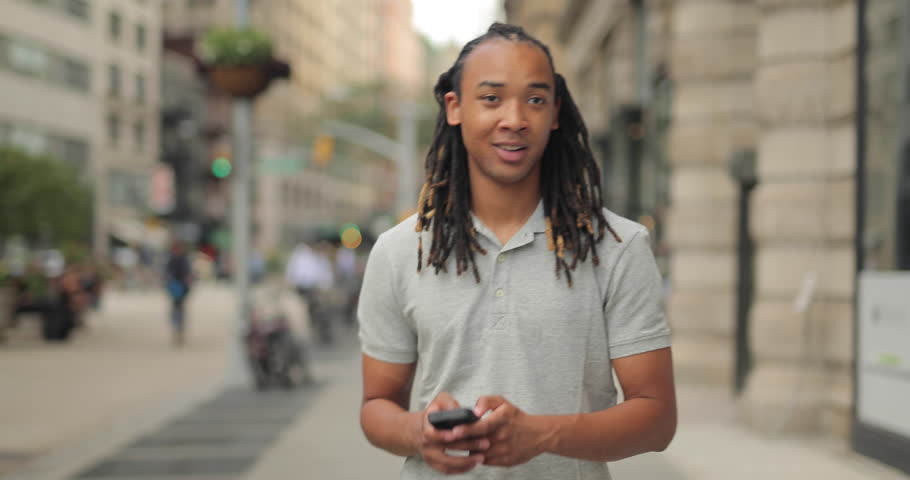Young African American Black Asian mixed man walking and texting on city street   Shutterstock HD Video #11427524