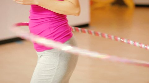 Fit woman doing hula hoop exercise in gym, closeup