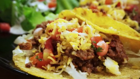 Soft Taco shells filled with mince meat, coriander and salsa on plate with salad