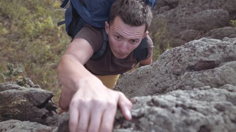 Man with backpack hiking and climbing the rocks, reaching the top of Ural Mountains. Shot in slow motion 50 fps