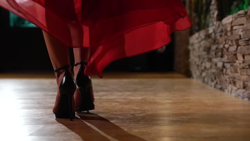 Female model in heels and red dress walking across wood floor