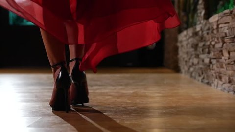 Female model in heels and red dress walking across wood floor