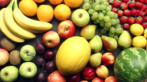 Different kinds of fresh fruit appearing on grey kitchen table - stop motion animation.