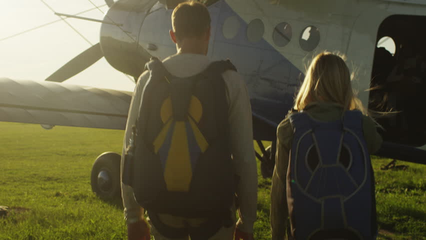 Man and Girl with Parachutes Moving out of the Plane. Shot on RED Cinema Camera in 4K (UHD).