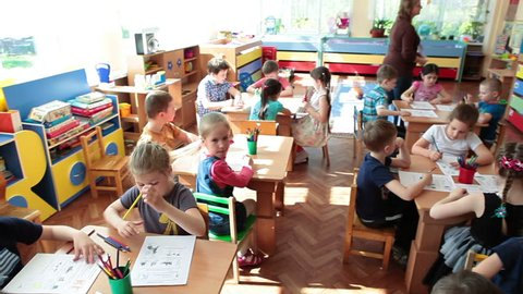 ST. PETERSBURG, RUSSIA - CIRCA MAY, 2015: Educators help children a pupils to drawing in daycare center at the skill lesson, preschool kids. Russian kindergarten is a preschool educational institution