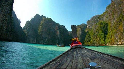 Video 4k - Onboard perspective of Phi-Phi Island's crystal clear waters and towering seacliffs from the weather worn deck of a motorized longtail boat in southern Thailand.