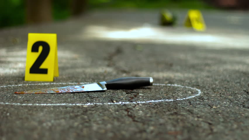 Crime scene with bloody knife and shoe that fell off. Yellow markers placed with the evidence.
